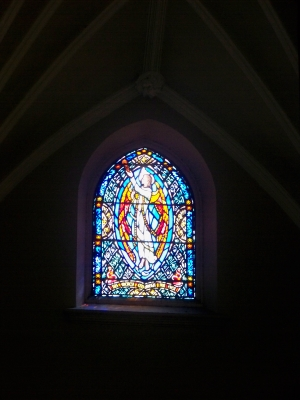 Small stained glass window towards the back of the church